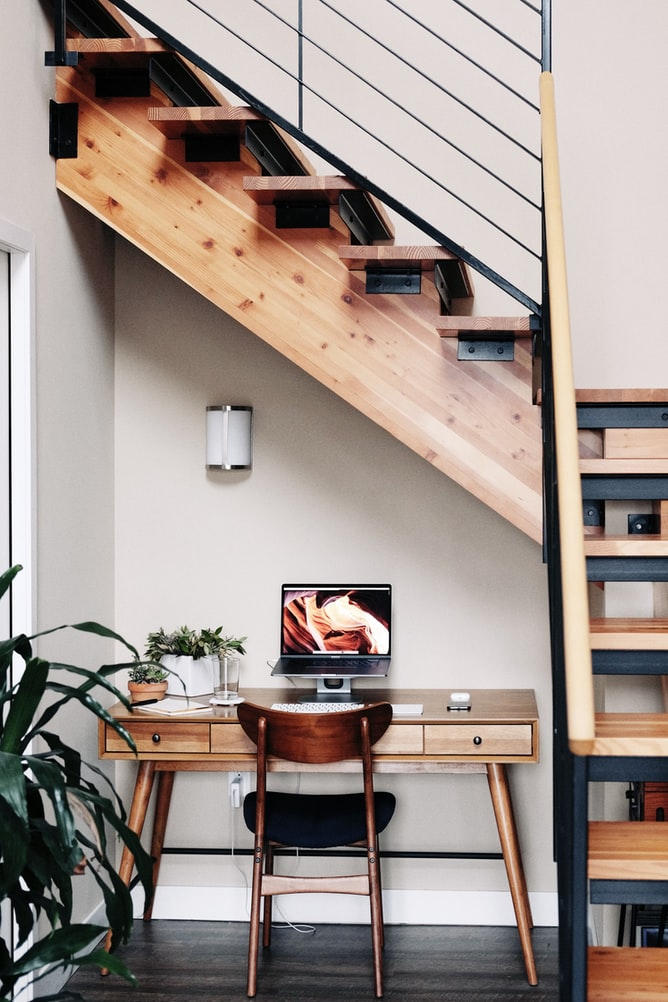chic desk set up underneath a set of stairs